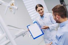 Doktor, der dem Patienten zahnmedizinische Ergebnisse zeigt lizenzfreies stockbild