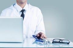 Doktor, der an dem Schreibtisch arbeitet stockbild