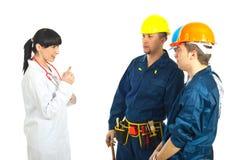 Doktor, der den Arbeitskraftmännern Rat gibt Stockbilder