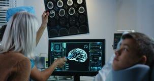Doktor, der Diagnose mit Patienten und seinem Verwandten bespricht stock footage