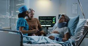 Doktor, der Diagnose mit Patienten und seinem Verwandten bespricht stock video