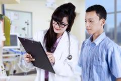 Doktor, der Diagnose Patienten erklärt Stockbild