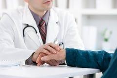 Doktor, der die Hand des Patienten hält Stockfotos