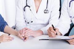 Doktor, der die Hand des Patienten hält Stockbilder