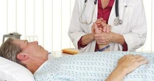 Doktor, der die Hand des Patienten hält und ihn tröstet Stockfoto