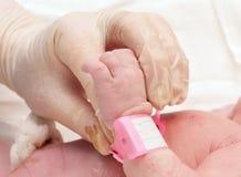 Doktor, der die Hand von einem neugeborenen hält Lizenzfreies Stockbild