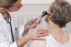 Doktor, der die Ohren des älteren Patienten überprüft stockfotos