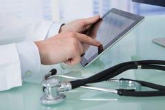 Doktor, der digitale Tablette am Schreibtisch verwendet Stockbilder