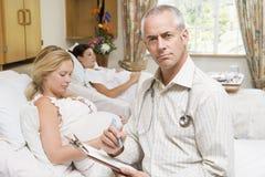 Doktor, der durch die schwangeren Frauen anhalten Diagramm sitzt Stockbilder