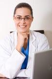 Doktor, der durch Laptop sitzt Lizenzfreie Stockfotografie