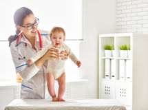 Doktor, der ein Baby überprüft Stockfotografie