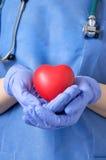 Doktor, der ein Herz hält Stockfotos