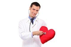 Doktor, der ein Kissen mit einem Stethoskop überprüft Lizenzfreie Stockfotos