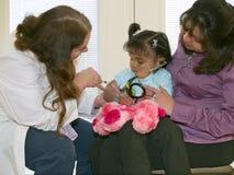 Doktor, der ein kleines Ureinwohnermädchen impft Lizenzfreies Stockfoto