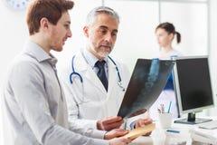 Doktor, der ein patient& x27 überprüft; s-Röntgenstrahl Stockbild