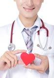 Doktor, der ein rotes Liebesherzkissen hält Lizenzfreie Stockfotos