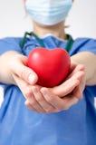 Doktor, der eine Herzform hält Lizenzfreie Stockbilder