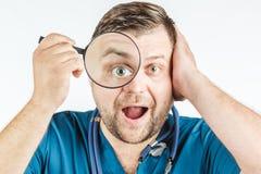 Doktor, der eine Lupe auf einem weißen Hintergrund verwendet Stockfotografie