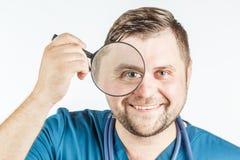 Doktor, der eine Lupe auf einem weißen Hintergrund verwendet Stockbild