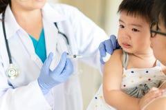 Doktor, der eine Spritze hält, um Impfstoff einzuspritzen Mutter ist umarmend er stockfotografie