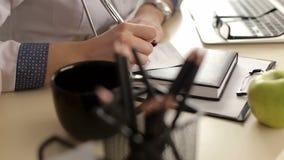 Doktor, der eine Verordnung auf seinen Schreibtisch schreibt stock video footage