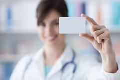 Doktor, der eine Visitenkarte hält Lizenzfreies Stockbild