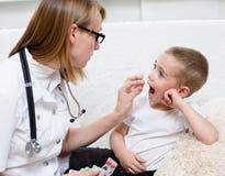 Doktor, der einem Kind eine Pille gibt Lizenzfreies Stockfoto