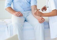 Doktor, der einem männlichen Patienten Impfstoff gibt Stockfotografie