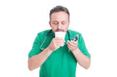 Doktor, der einen Bruch trinkt frischen Kaffee hat Stockbilder