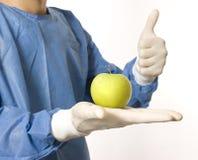 Doktor, der einen grünen Apfel anhält Lizenzfreies Stockbild