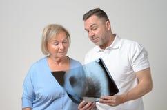 Doktor, der einen Röntgenstrahl mit einem Patienten bespricht lizenzfreie stockfotografie