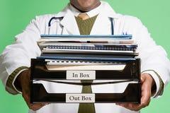 Doktor, der einen Stapel Schreibarbeit hält Stockfotografie