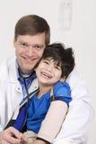 Doktor, der einen untauglichen kleinen Jungen anhält Stockbild