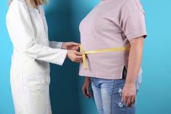 Doktor, der fette Frau ` s Taille misst lizenzfreie stockfotografie