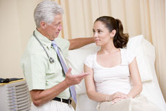 Doktor, der Frauenüberprüfung im Prüfungraum gibt Stockfoto