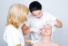 Doktor, der geduldige Frauenhaut überprüft Stockbild