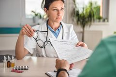 Doktor, der geduldiges Anmeldeformular empfängt lizenzfreie stockfotografie