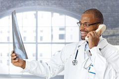 Doktor, der gute Nachrichten am Telefon erklärt Lizenzfreie Stockfotografie