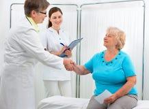 Doktor, der Hände mit Patienten rüttelt Stockbild