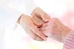 Doktor, der Hand der älteren Dame anhält Lizenzfreie Stockfotos