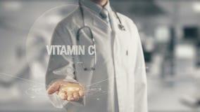 Doktor, der in der Hand Vitamin C hält Stockfoto