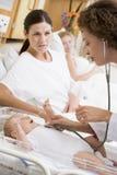 Doktor, der Herzschlag des Schätzchens mit neuer Mutter überprüft Lizenzfreies Stockbild