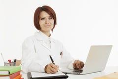 Doktor, der hinter ihrem Schreibtisch sitzt Stockbilder