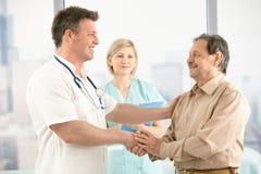 Doktor, der Hände mit älterem Patienten rüttelt Stockfotografie
