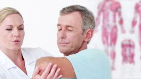 Doktor, der ihren geduldigen Arm ausdehnt stock video footage