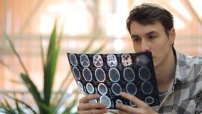 Doktor in der informellen Kleidung hält Röntgenaufnahme in seinen Händen und denkt stock video footage