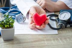 Doktor der Innerer Medizin und Kardiologe, der in seinen Händen und in Shows zur geduldigen Zahl des Herzens der roten Karte währ lizenzfreie stockfotografie