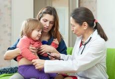 Doktor, der 2 Jahre Baby mit Stethoskop überprüft Stockbilder