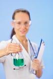 Doktor der jungen Frau, der medizinische Retorte zeigt lizenzfreie stockfotos