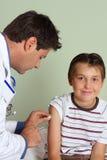 Doktor, der Kindimpfstoff einspritzt stockfotografie